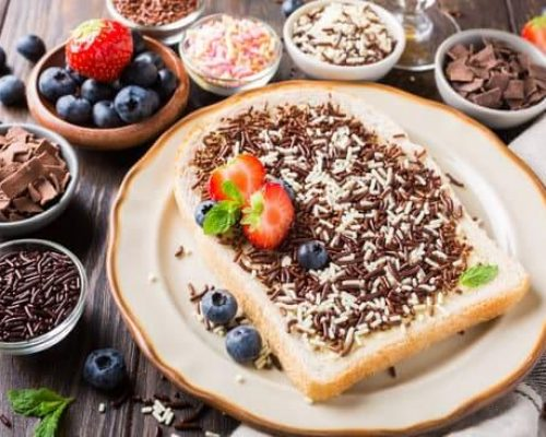 Dutch breakfast, slice of bread with hagelslag chocolate sprinkles and berries.
