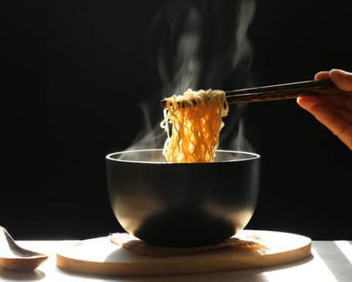 Woman hand holding chopsticks of instant noodles in cup with smoke rising dark background, Sodium diet high risk kidney failure, Healthy eating concept
